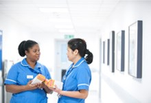 Two nurses talking in corridor